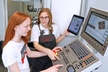 <p>Eva Dohles (right) took part in Girls' Day at Brose herself four years ago. Now the 17-year-old is completing her apprenticeship training as a tool and die maker and showed high-school student Emily Young (14) how to program a CNC milling machine.</p>